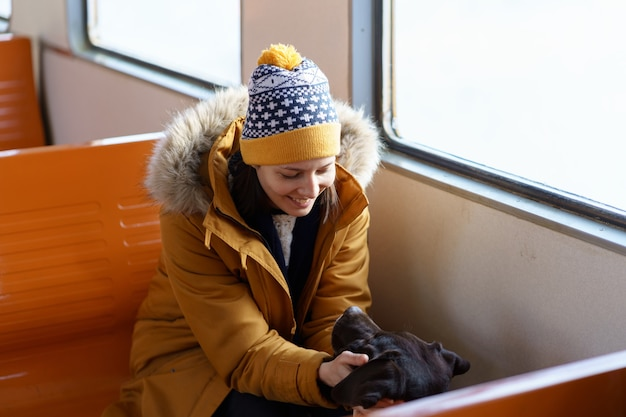 Happy girl wear winter clothes sitting in local train talking with her lovely dog traveling together Premium Photo