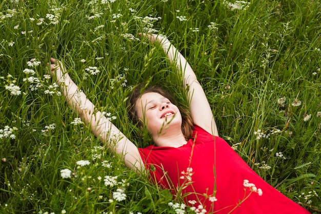 Happy girl with closed eyes lying on grass in beautiful nature Free Photo