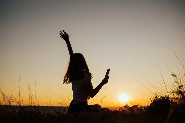 Счастливая девушка с рукой поет и слушает музыку в наушниках в поле на удивительном закате. Premium Фотографии