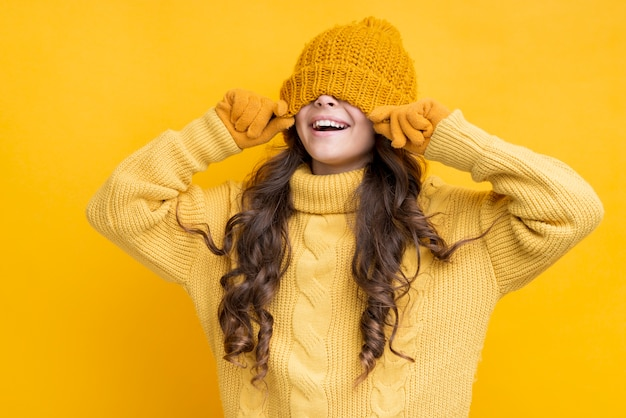 Happy girl with hat pulled over his eyes Free Photo