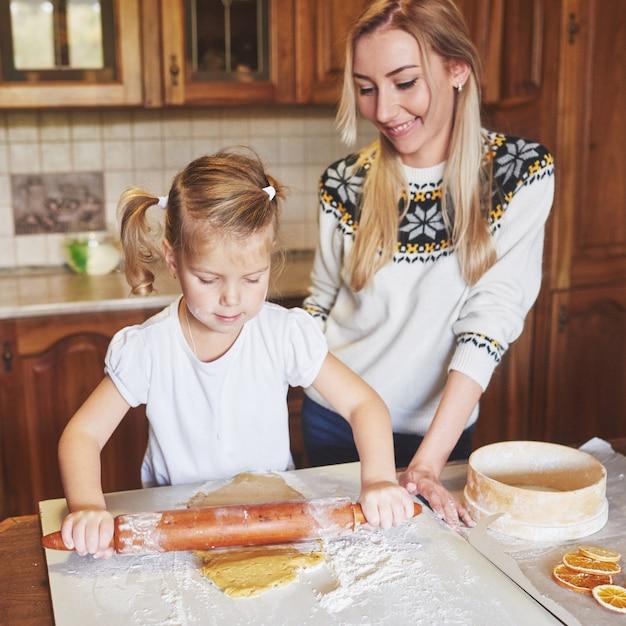 彼女の母親と一緒に幸せな女の子はクッキーを調理します。 無料写真
