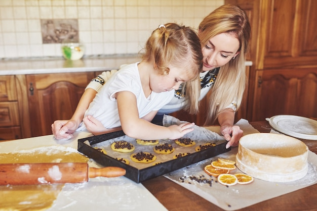 Happy girl with her mother cook cookies. Free Photo