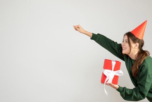 Счастливая девушка в кепке в позе супергероя держит подарок на белом Бесплатные Фотографии
