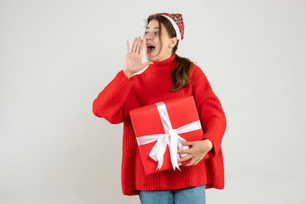 Happy girl with santa hat holding gift calling someone on white Free Photo