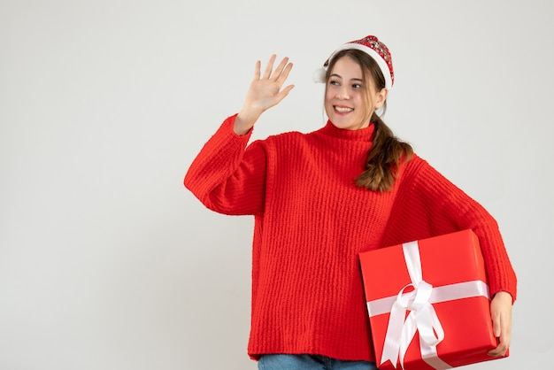 Happy girl with santa hat holding gift and hailing someone on white Free Photo