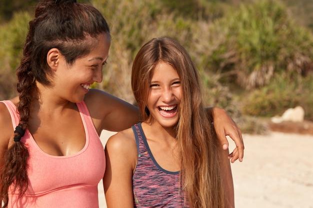 ビーチを散歩している間、幸せなガールフレンドは寄り添い、前向きにクスクス笑い、楽しい瞬間を楽しんで、熱帯の国で休んでいます 無料写真