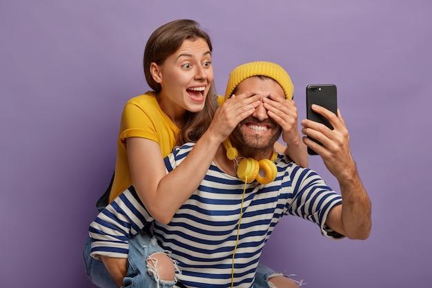 幸せなガールフレンドはピギーバックに乗って、彼氏が目を覆って楽しんで、驚きを準備します。陽気なヒップスターがスマートフォンを前に持っている 無料写真