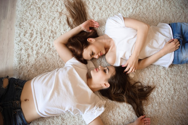 Happy girlfriends lying on back top view sisters. Premium Photo
