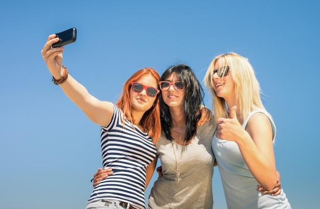 Happy girlfriends taking selfie against blue sky Premium Photo