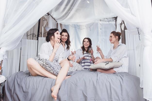 Happy girls in white men's shirts that celebrate a bachelorette party Premium Photo