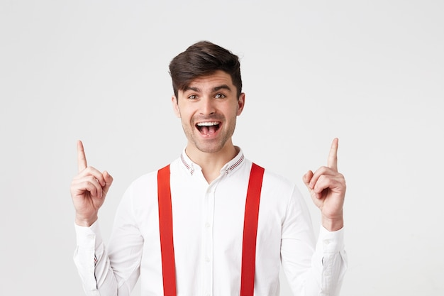 Felice bel ragazzo felice, sembra stupito eccitato, vestito con camicia bianca e bretelle rosse, punta con l'indice verso l'alto Foto Gratuite