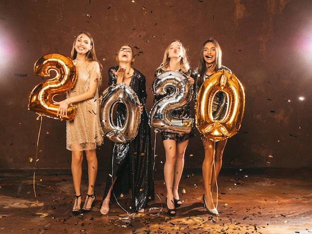 Happy gorgeous girls in stylish sexy party dresses holding gold and silver 2020 balloons Free Photo