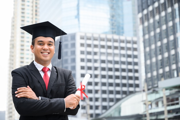 Happy graduate. happy asian man in graduation gowns holding diploma in hand on urban city Premium Photo