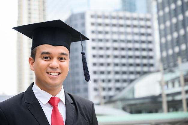 Счастливый выпускник. счастливый азиатский человек в мантиях градации держа диплом в руке на городском городе. Premium Фотографии