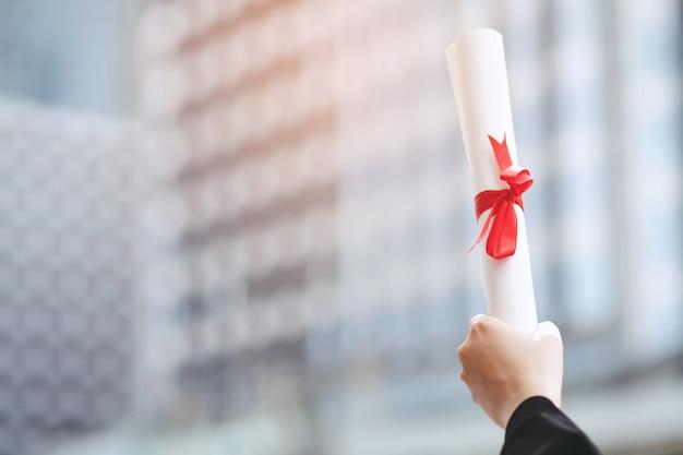 Счастливая молодая женщина выпускника носить черное платье положила руки вверх сертификат. диплом с красной лентой с фоном здания школы, концепция образования Premium Фотографии