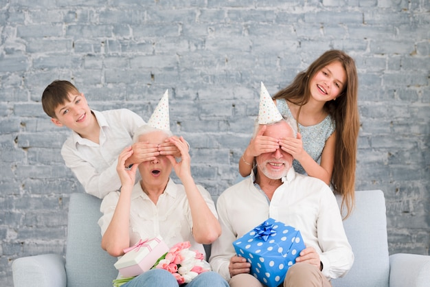 Happy grandchildren covering their grandparents eyes at birthday party Free Photo