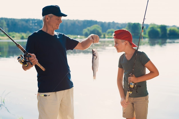 Happy grandfather and grandson fishing on river. Premium Photo