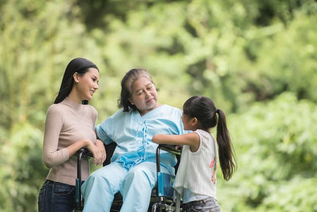 happy grandmother in wheelchair with her daughter and grandchild in