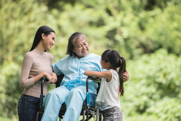 Happy grandmother in wheelchair with her daughter and grandchild in a park, happy life happy time. Free Photo