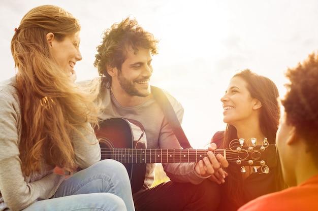 夏の屋外ギターを弾き、一緒に歌う友人の幸せなグループ Premium写真