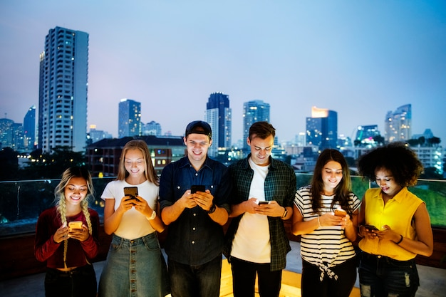 Happy group of young adults using smartphones in the cityscape Premium Photo