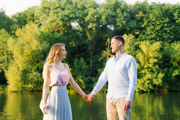 Happy guy and girl smile and hold hands Premium Photo