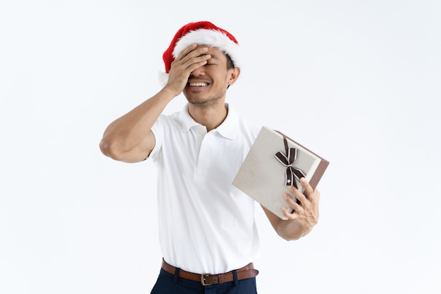 Happy guy trying to guess what is inside christmas gift box Free Photo
