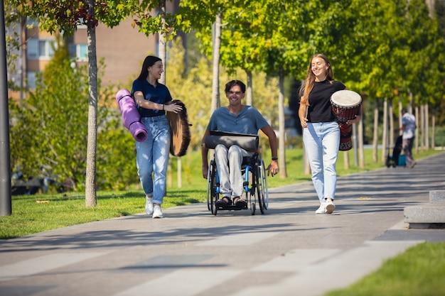 Felice handicappato uomo su una sedia a rotelle di trascorrere del tempo con gli amici che suonano musica strumentale dal vivo all'aperto. Foto Gratuite