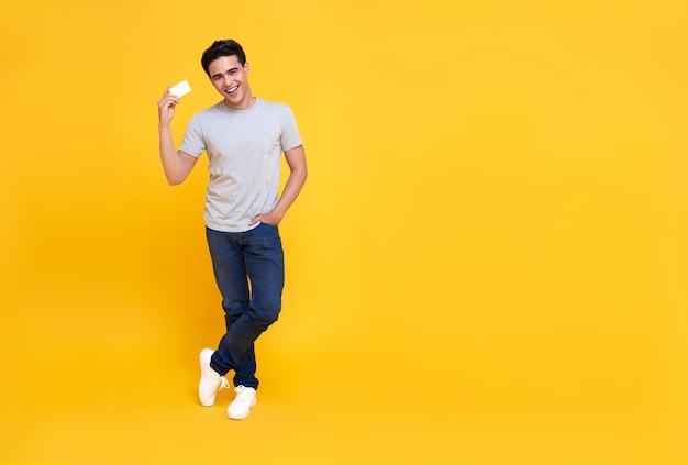 黄色の手にクレジットカードを示す幸せなハンサムなアジアの買い物中毒の男。 Premium写真