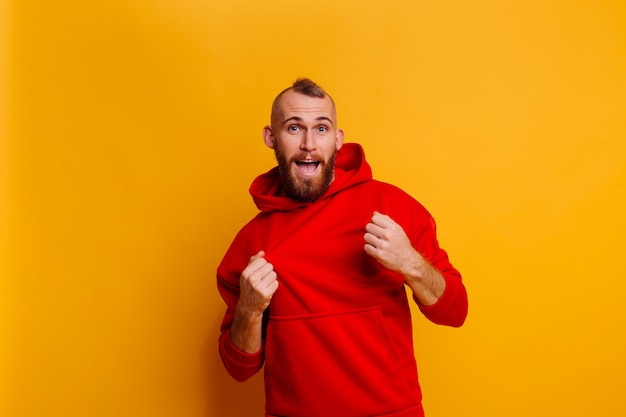 Happy handsome brutal bearder man wearing warm red winter trendy fleece hoodie Free Photo
