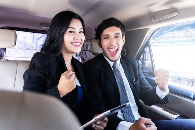 Happy handsome businessman and business woman sitting in luxury limousine car, working on laptop computer, works anytime and anywhere concept. Premium Photo