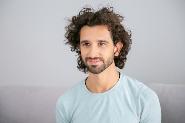 행복 잘 생긴 곱슬 머리 젊은 남자 캐주얼 티셔츠를 입고 집에서 소파에 앉아 멀리보고 웃 고. 남성 초상화 개념 무료 사진