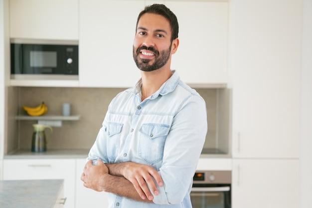 腕を組んでキッチンでポーズをとって幸せなハンサムな暗い髪のラテン男 無料写真