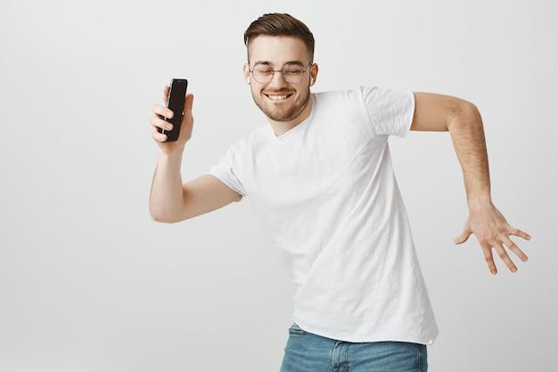 手に携帯電話を持つワイヤレスイヤホンで音楽に合わせて踊るメガネで幸せなハンサムな男 無料写真