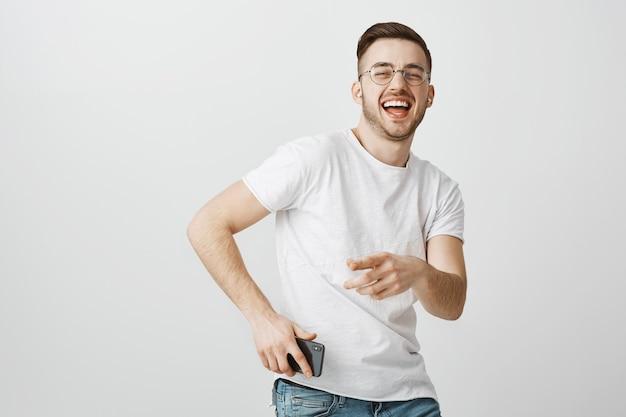 Счастливый красивый парень в очках танцует под музыку в беспроводных наушниках с мобильным телефоном в руке Бесплатные Фотографии