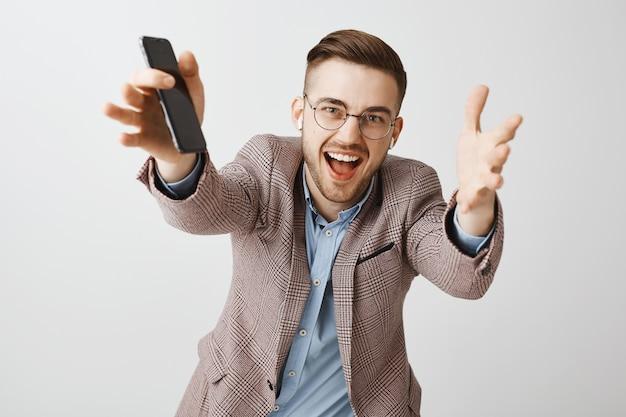 Felice imprenditore maschio bello che raggiunge le mani in avanti, ascoltando musica con auricolari wireless e playlist nell'app del telefono cellulare Foto Gratuite