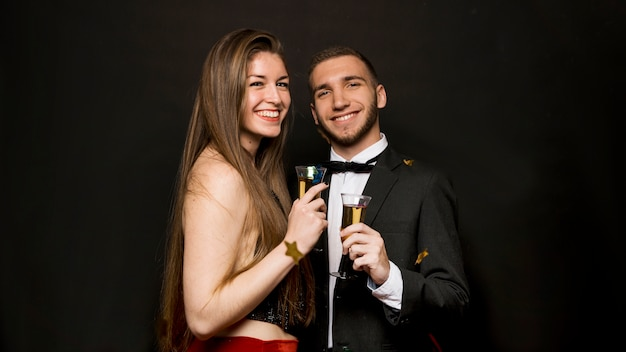 Happy handsome man and attractive woman with glasses of drinks and confetti Free Photo