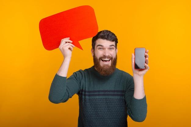 Счастливый красавец держа красный пузырь речи и показывая экран смартфона, лучшее предложение Premium Фотографии