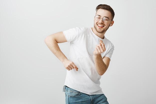 Счастливый красавец в очках танцует, слушает музыку в беспроводных наушниках Бесплатные Фотографии