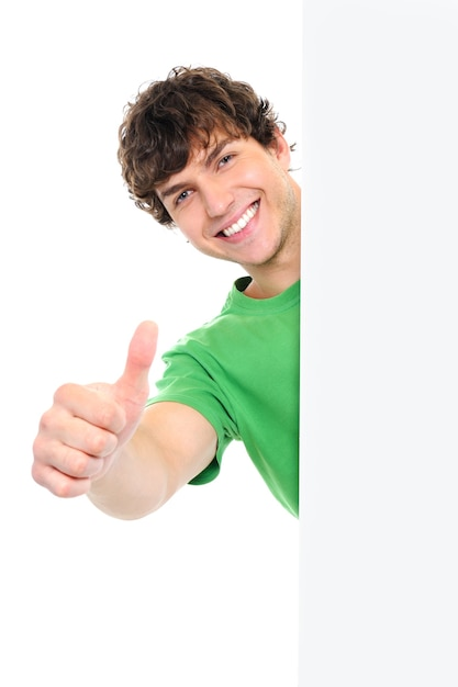 Happy handsome man showing thumbs up look out from white blank banner Free Photo