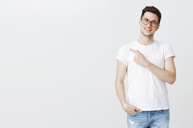 Счастливый красивый молодой студент-мужчина в очках, указывая пальцем влево на copyspace Бесплатные Фотографии