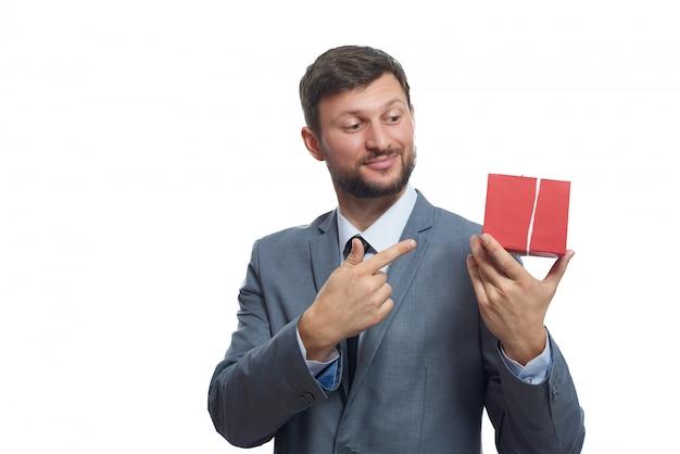 Felice bel giovane uomo in una tuta sorridente che punta al contenitore di regalo Foto Gratuite