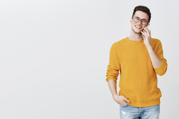Felice bel giovane uomo parla al telefono e sorridente Foto Gratuite