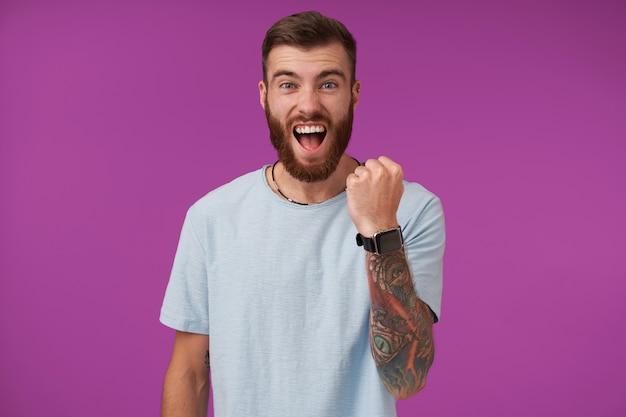幸せなハンサムな若い入れ墨ブルネットの男は、カジュアルな服を着て紫色でポーズをとっている間、上げられた握りこぶしを維持し、元気に叫んでいるひげを持つ 無料写真