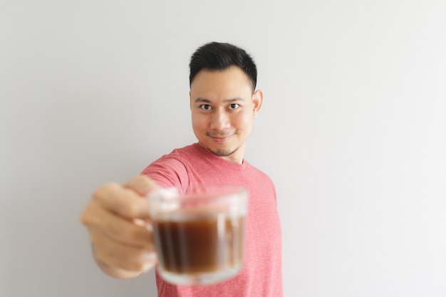 Happy healthy man in red t-shirt drinks coffee or asian herbs drink. Premium Photo