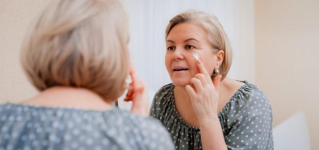 ミラーで幸せな健康な成熟した女性は顔にアンチエイジング保湿化粧品クリームを適用し、笑顔の中年女性ソフトクリーンスキンケアと美容 Premium写真