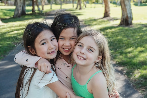 Happy and healthy mixed ethnic young little girls hugging and smiling in the park, best friends and friendship Premium Photo