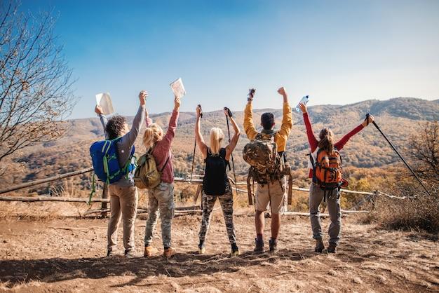 Счастливые туристы, стоя на поляне с руками в воздухе и глядя на прекрасный вид Premium Фотографии