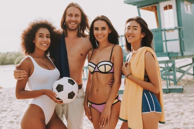 Happy hipster man and beach football girls team Premium Photo