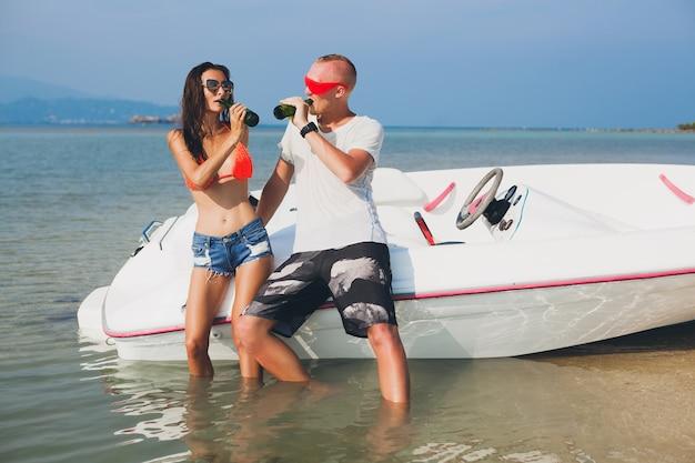 Счастливые битник женщина и мужчина пьют пиво на летних тропических каникулах в таиланде, путешествуя на лодке в море, вечеринка на пляже, люди веселятся вместе, положительные эмоции Бесплатные Фотографии